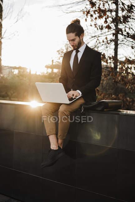 Businessman using laptop while sitting on retaining wall during sunset — Stock Photo