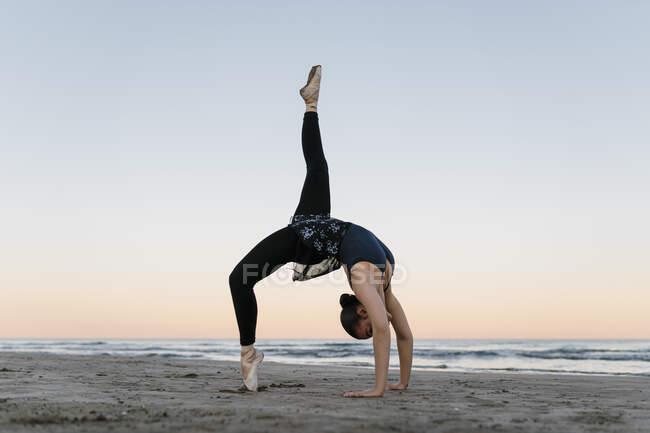 Гибкий балетный танцор, загибающийся набок, тренируясь на пляже против неба — стоковое фото