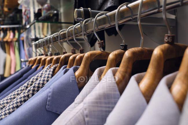 Fila de camisas em rack em alfaiates boutique — Fotografia de Stock