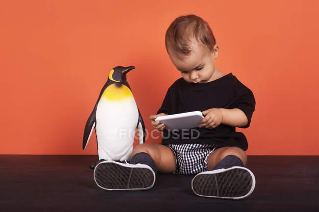 Baby girl ignoring toy while using mobile phone sitting against orange background — Stock Photo