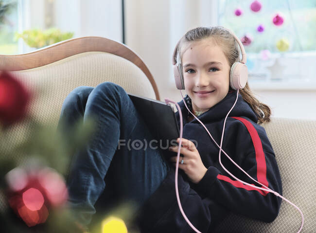 Chica sonriente escuchando música en la tableta digital mientras se sienta en el sofá en casa durante la Navidad - foto de stock
