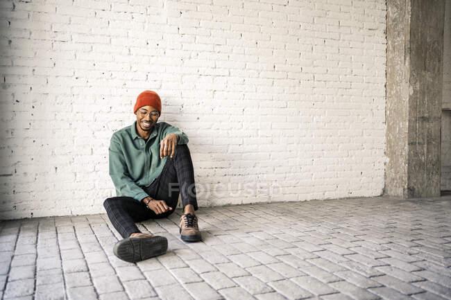 Hombre feliz en sombrero de punto sentado en el suelo contra la pared de ladrillo blanco - foto de stock