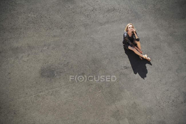 Contemplando mulher sentada na estrada — Fotografia de Stock