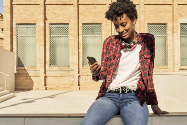 Sorrindo jovem mulher usando telefone celular enquanto sentado contra a construção — Fotografia de Stock