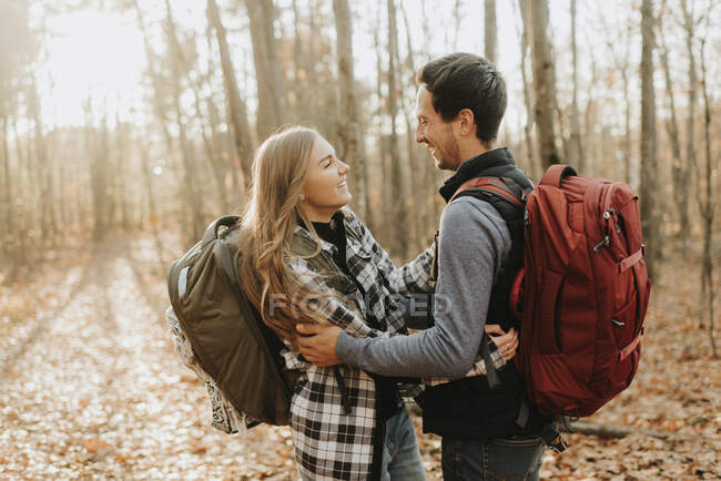 Young couple embracing in forest during autumn hike — Stock Photo