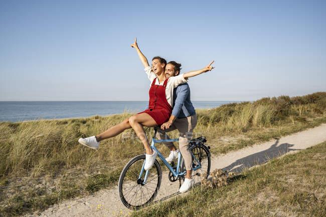 Mulher com a mão levantada sentado no punho enquanto desfruta de passeio de bicicleta com namorado contra céu limpo — Fotografia de Stock