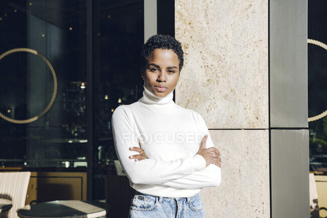 Confident businesswoman standing with arms crossed at cafe — Stock Photo