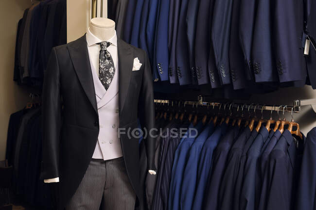 Tailcoat withformal striped trouserson mannequin and blazers on rack in tailors boutique — Stock Photo