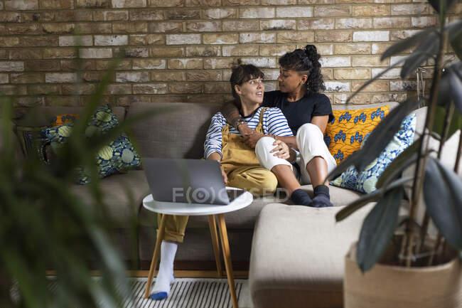 Молода лесбіянка дивиться один на одного, сидячи вдома на дивані. — стокове фото