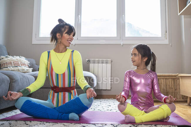 Мать и дочь практикуют йогу в гостиной дома — стоковое фото