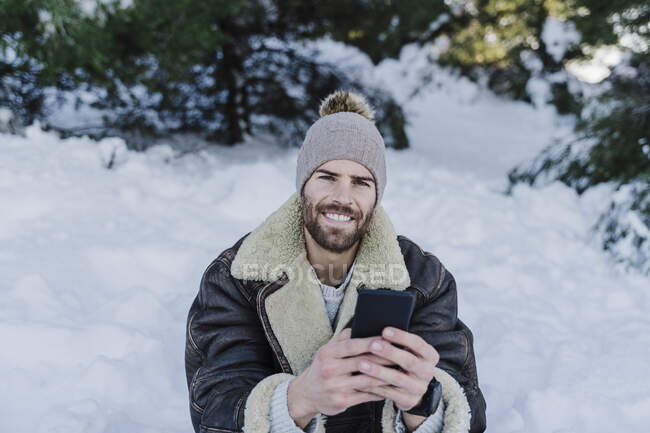 Smiling young man holding mobile phone while sitting in snow — Stock Photo