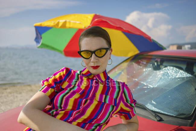 Приваблива жінка в сонячний день спирається на машину на пляжі. — стокове фото