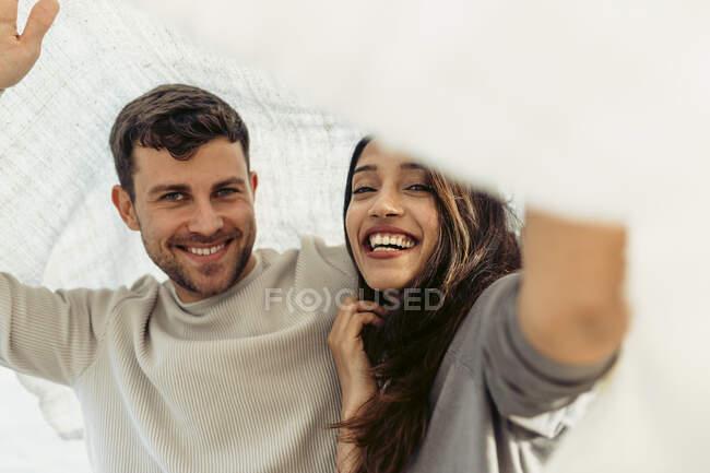 Sonriente novia y novio pasar tiempo libre por debajo del chal - foto de stock