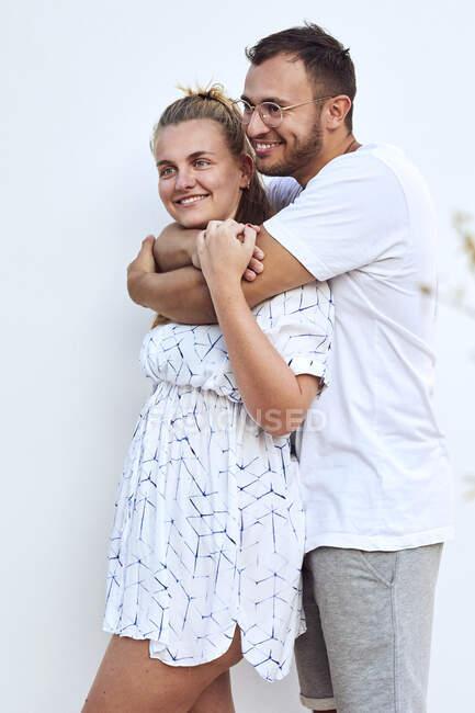 Улыбающаяся молодая пара смотрит в сторону, стоя напротив белой стены — стоковое фото