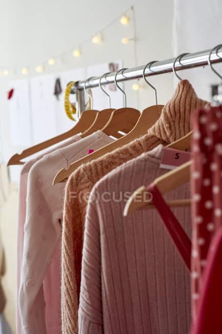 Cremalheira de roupa com variação de roupa feminina no atelier — Fotografia de Stock