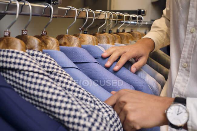 Clienti mani di navigazione camicie su rack in sartoria boutique — Foto stock