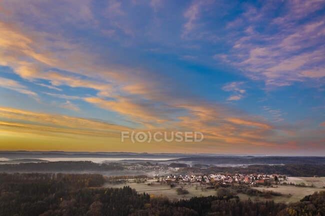 Drone vista del cielo lunatico sul villaggio di campagna all'alba autunnale nebbiosa — Foto stock