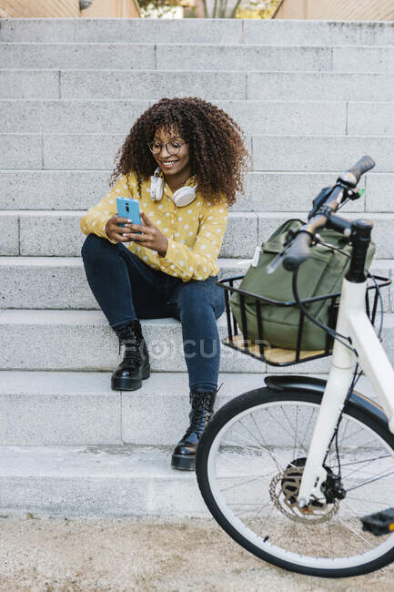 Smiling woman using mobile phone while sitting on steps — Stock Photo
