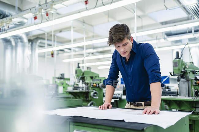 Empreendedor masculino olhando sobre o plano de chão enquanto trabalhava na mesa na fábrica — Fotografia de Stock