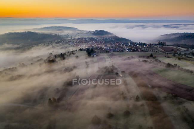 Germania, Baden-Wurttemberg, Berglen, Drone vista del villaggio avvolto nella fitta nebbia all'alba — Foto stock