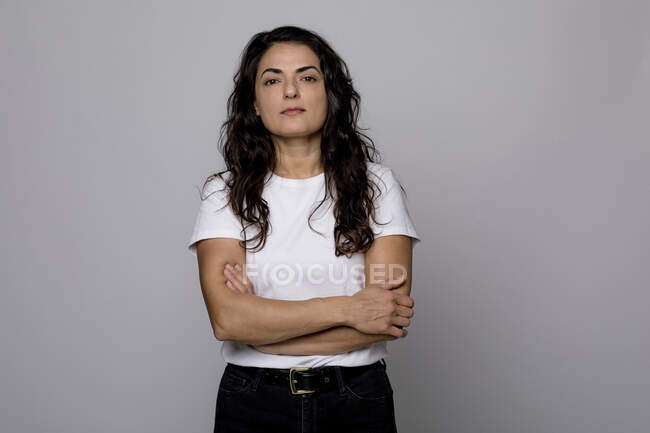 Confident woman standing with arms crossed against gray background — Stock Photo