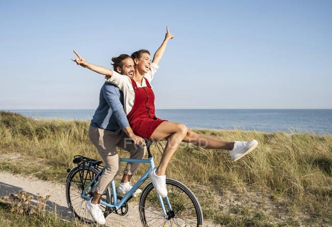 Беззаботная пара наслаждается велосипедной прогулкой по ясному небу — стоковое фото