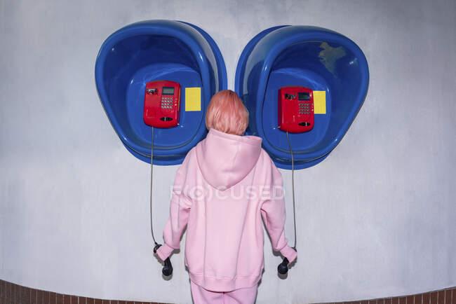 Передній вигляд молодої жінки з рожевим волоссям, одягненої в рожевий капелюх сорочки, що стоїть перед телефонними будками. — стокове фото