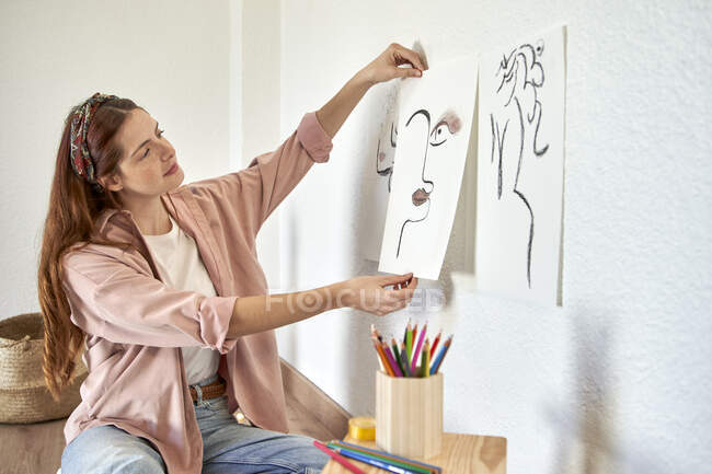 Female artist pasting charcoal drawing on wall in living room — Stock Photo