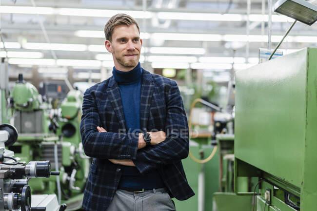 Empresário sorridente com braços cruzados olhando para longe enquanto estava parado perto de equipamentos de máquinas na fábrica — Fotografia de Stock