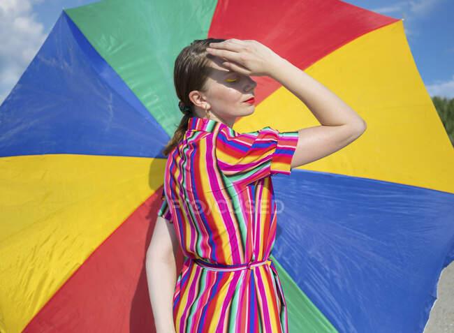 У сонячний день серед дорослої жінки барвистою парасолькою на пляжі. — стокове фото