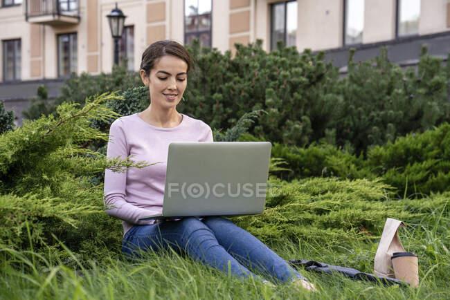 Молода бізнес-леді, яка користується ноутбуком, сидячи в парку. — стокове фото