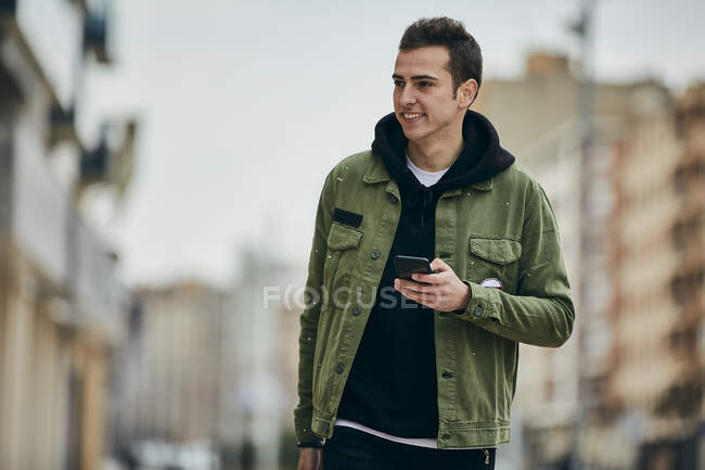 Handsome man looking away while holding mobile phone - foto de stock