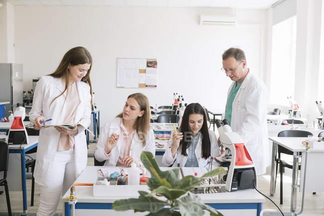 Студенти і викладач у білих плащах обговорюють на уроках науки. — стокове фото