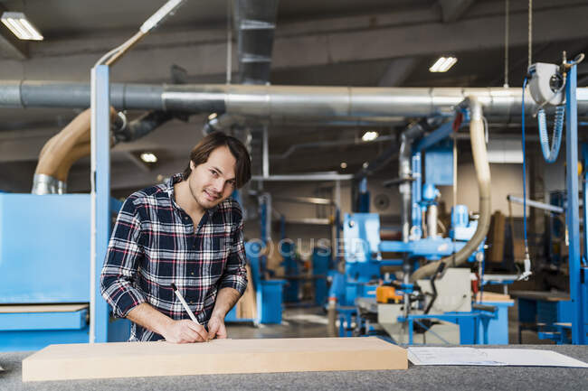 Smiling expertise measuring wood while working at industry — Stock Photo