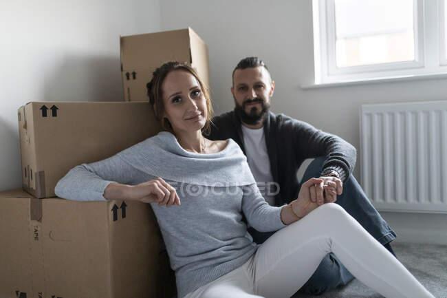Молодая женщина, держась за руку парня, опираясь на картонные коробки в новом доме — стоковое фото