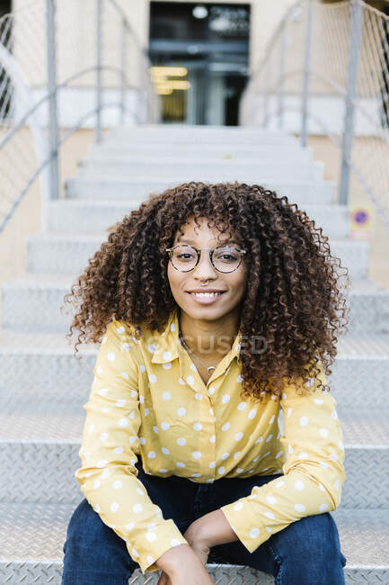 Mujer joven sonriendo mientras está sentada en los escalones - foto de stock