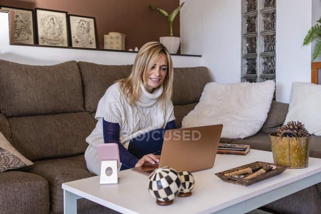 Доросла жінка-терапевт працює на ноутбуці в офісі. — стокове фото