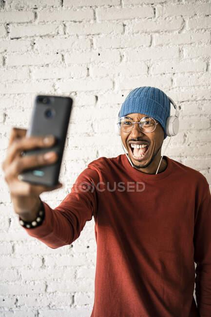 Hombre alegre con la boca abierta tomando selfie mientras escucha música contra la pared de ladrillo blanco - foto de stock