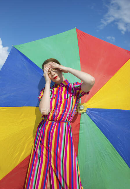Carefree woman against colorful beach umbrella on sunny day — Stock Photo