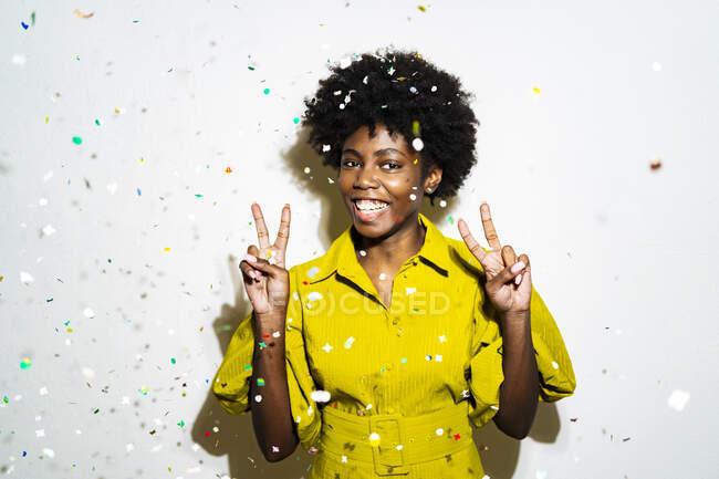 Donna sorridente gesticolando segno di pace mentre in piedi in mezzo a coriandoli sullo sfondo bianco — Foto stock