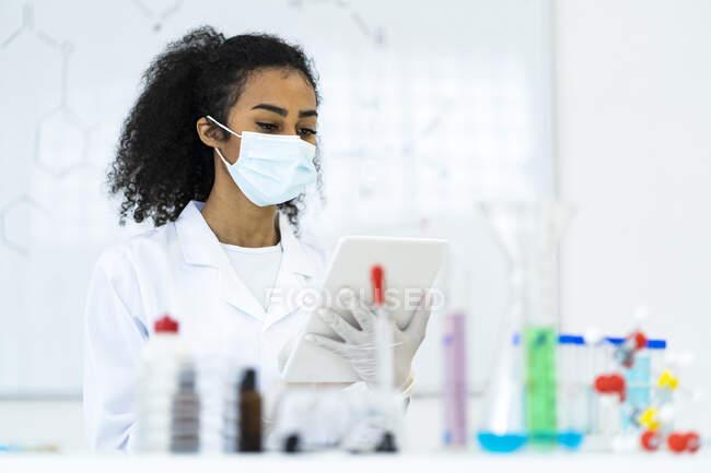 Молодой исследователь, использующий цифровой планшет во время работы в лаборатории во время пандемии — стоковое фото