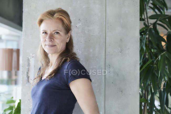 Mujer madura sonriente de pie por columna en apartamento loft en casa - foto de stock