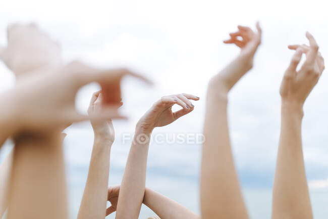 Female friends with raising arms against sky — Stock Photo