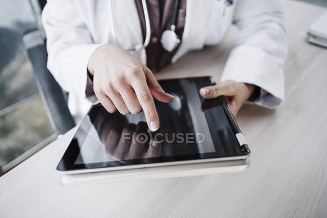 Experiencia médica femenina utilizando mesa digital en el escritorio en el hospital - foto de stock