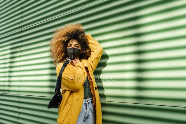 Afro mulher com mão no cabelo segurando cintura pacote por parede verde durante a pandemia — Fotografia de Stock