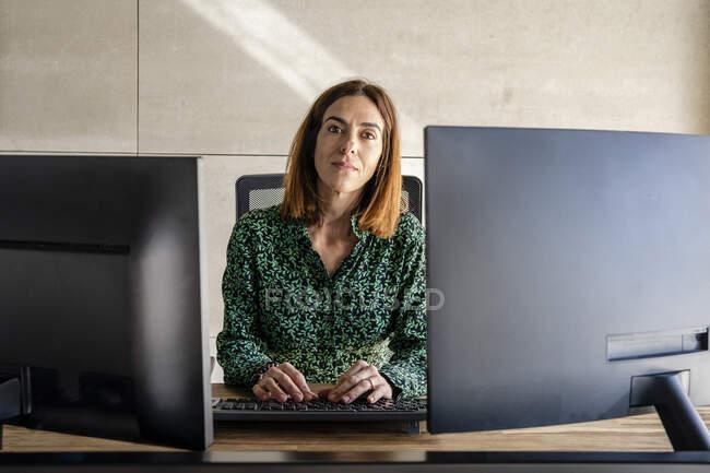 Empresaria con computadora sentada en el escritorio en la oficina - foto de stock