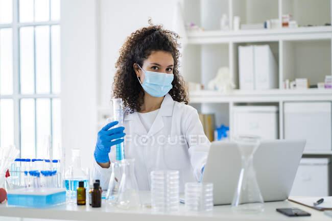 Jovem cientista com tubo de teste e laptop no hospital durante o COVID-19 — Fotografia de Stock