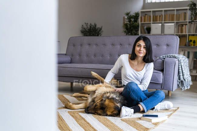 Молодая женщина гладит собаку, сидя на ковре напротив дивана в гостиной — стоковое фото