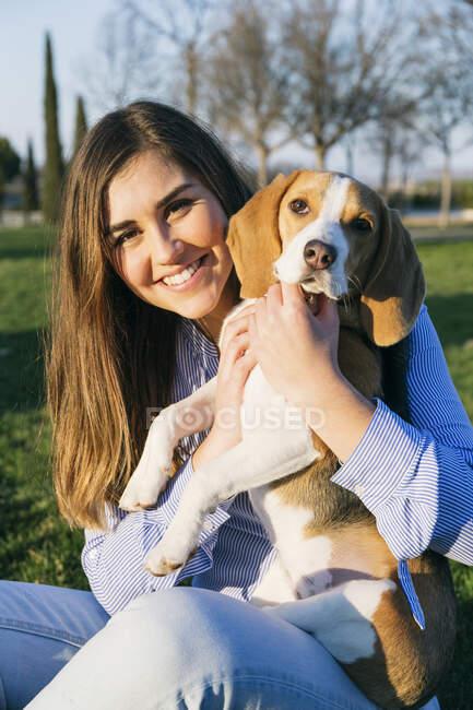 Mujer adulta sentada con el perro en el parque al atardecer - foto de stock