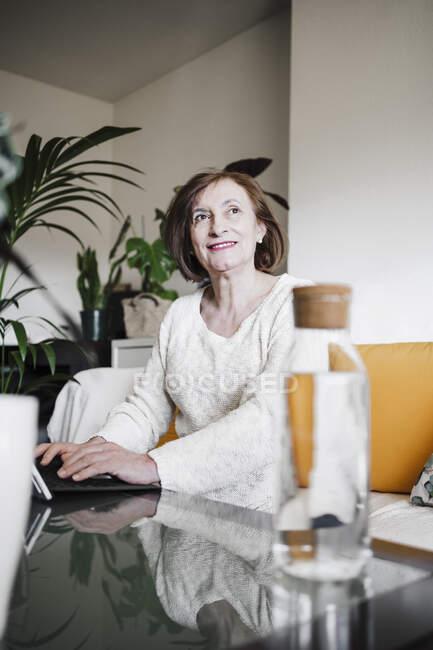 Усміхнена жінка, яка дивиться у далечінь, користуючись ноутбуком удома. — стокове фото